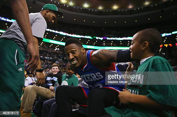 Robert Covington of the Philadelphia 76ers climbs out of court side seats after falling into a group of fans during the third quarter against the...