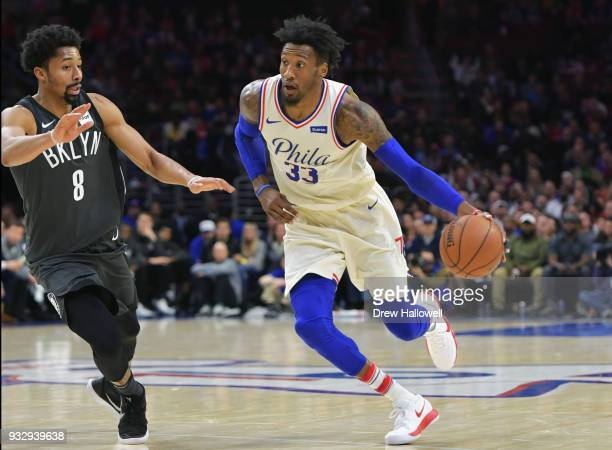 Robert Covington of the Philadelphia 76ers drives past Spencer Dinwiddie of the Brooklyn Nets at the Wells Fargo Center on March 16 2018 in...