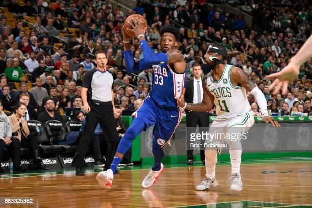 Robert Covington of the Philadelphia 76ers handles the ball against Kyrie Irving of the Boston Celtics on November 30 2017 at the TD Garden in Boston...