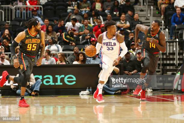 Robert Covington of the Philadelphia 76ers jocks for a position against Dewayne Dedmon and DeAndre' Bembry of the Atlanta Hawks during the game on...