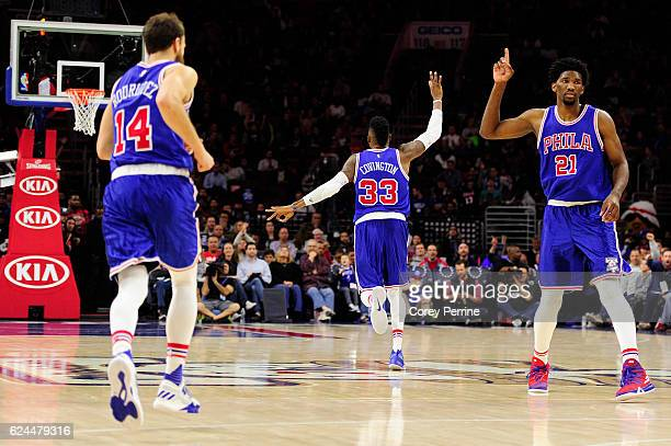 Robert Covington of the Philadelphia 76ers reacts to a threepointer as teammates Joel Embiid reacts along and Sergio Rodriguez who runs downcourt...