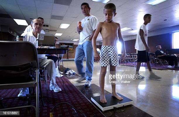 DENVER CO JUNE 28 2003 Robert <cq> Baca <cq> President and Head Coach of Baca Boxing Club <cq> watches over as Weigh Master John < Ulibarri <cq> a...