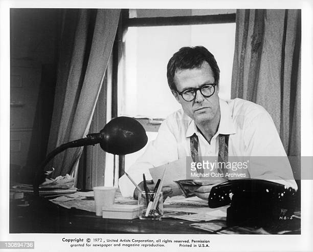 Robert Culp examines bills in a scene from the film 'Hickey And Boggs' 1972
