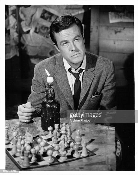 Robert Culp sitting at a table that has a chess board and lit candle on it in a scene from the television series 'I Spy' 1965