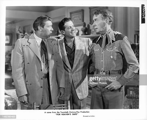 Robert Cummings puts his arms around Clifton Webb and Harry von Zell in a scene from the film 'For Heaven's Sake' 1950