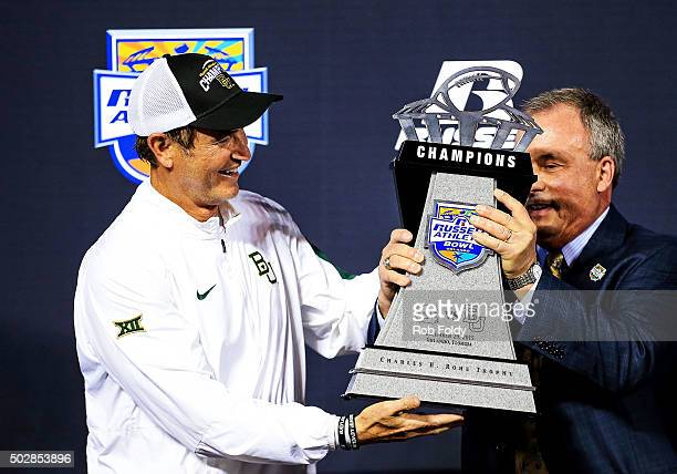 Robert Davis, vice president and GM of Russell Athletic, hands the chapionship trophy to head coach Art Briles of the Baylor Bears after the Russell...