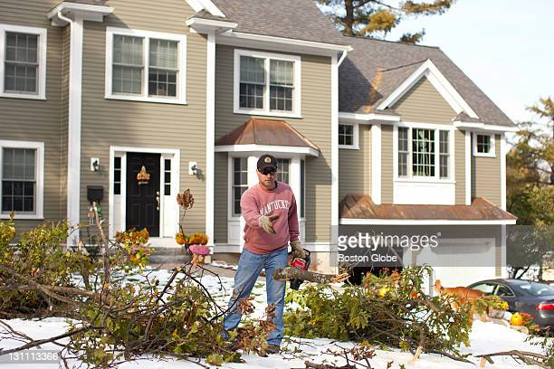 Robert Davy cleared fallen branches in front of his Lexington home while his two young sons were at a movie because they were getting cabin fever...