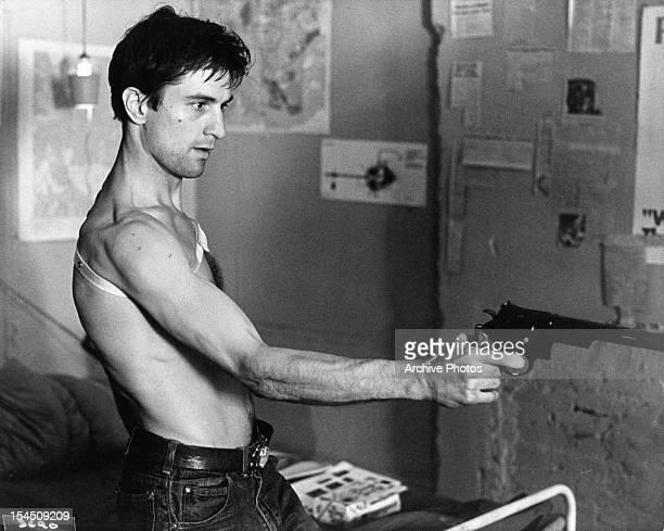 Robert De Niro points a gun in a scene from the film 'Taxi Driver' 1976