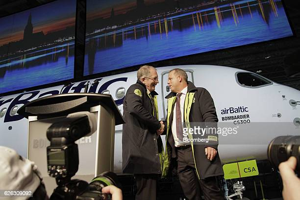 Robert Dewar vice president and general manager of CSeries at Bombardier Inc left and Martin Gauss chief executive officer of airBaltic shake hands...