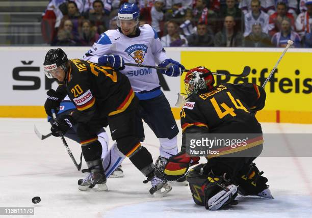 Robert Dietrich of Germany and Janne Lahti of Finland battle for the puck during the IIHF World Championship qualification match between Germany and...