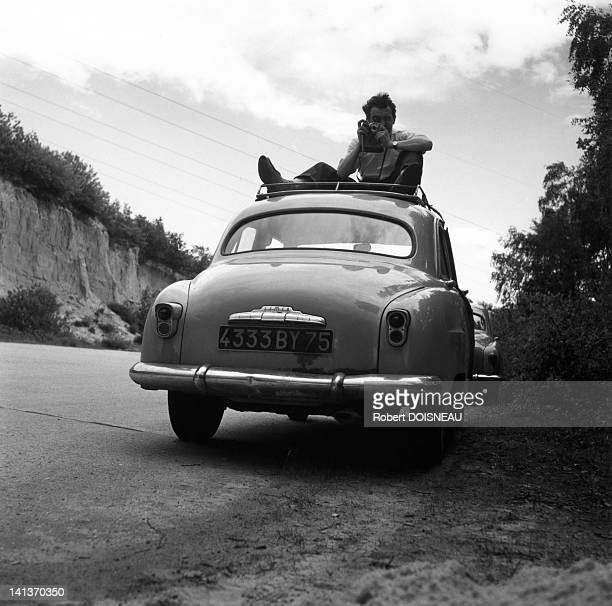 Robert Doisneau on the roof of his Simca Aronde car France in 1954