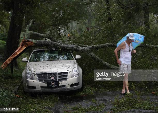 Robert Dolman walks past a Cadillac that has a large tree limb on it on September 16 2018 in Wilmington North Carolina Hurricane Florence hit...