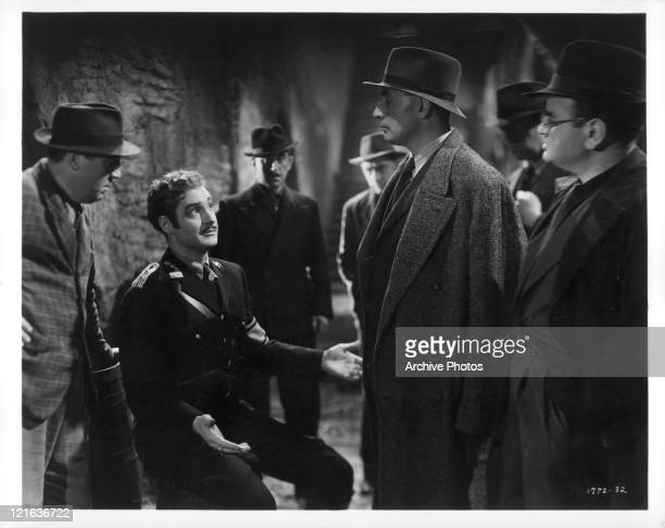 Robert Donat sits with palms up with unknown actors in a scene from the film 'Adventures of Tartu' 1943