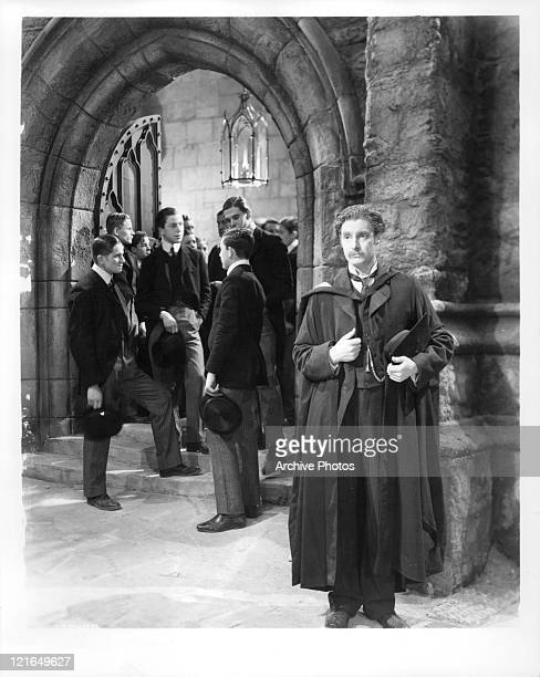 Robert Donat standing in a trench coat with his hat in his hand in a scene from the film 'Goodbye Mr Chips' 1939