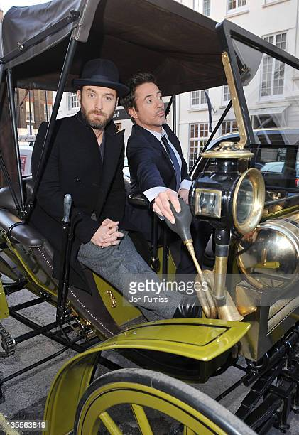 Robert Downey Jr and Jude Law the cast Of Sherlock Holmes A Game Of Shadows pose outside Claridge's Hotel on December 12 2011 in London England