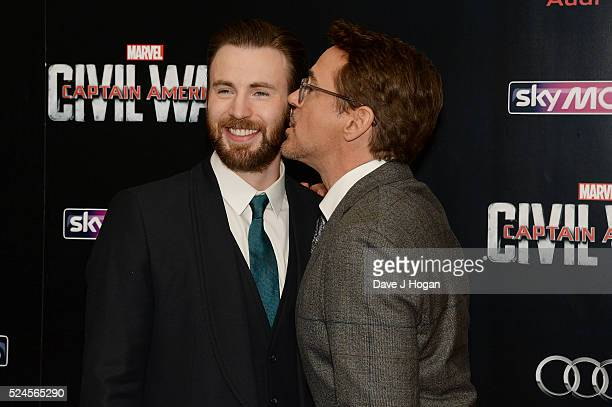Robert Downey Jr kisses Chris Evans during the European film premiere of 'Captain America Civil War' at Vue Westfield on April 26 2016 in London...