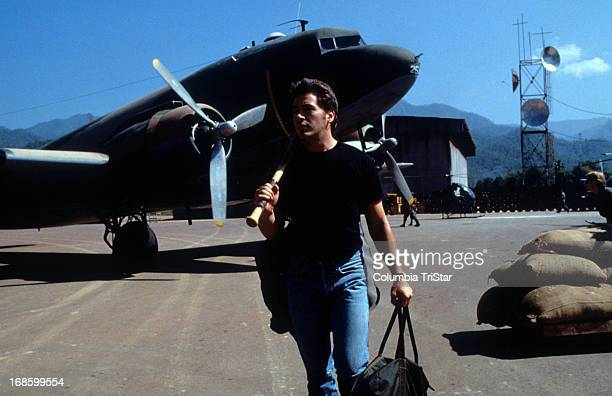Robert Downey Jr walking on airfield with bat in a scene from the film 'Air America' 1990