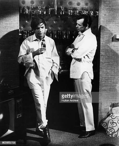 Robert Drivas accepts a drink from this father David Janssen in a scene for the United Artist movie Where It's At circa 1968