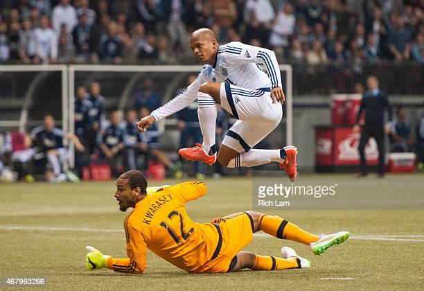 Robert Earnshaw of the Vancouver Whitecaps FC jumps over goalkeeper Adam Kwarasey of the Portland Timbers while watching his shot go in for the game...