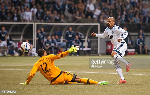 Robert Earnshaw of the Vancouver Whitecaps FC shoots the ball past goalkeeper Adam Kwarasey of the Portland Timbers for the game winning goal in MLS...