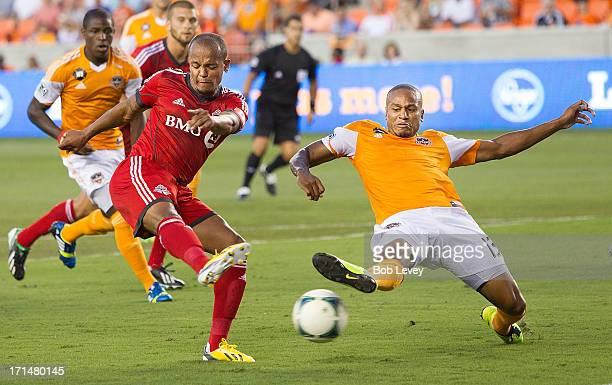 Robert Earnshaw of Toronto FC shoors on goal as Ricardo Clark of Houston Dynamo attempts to defelect the ball at BBVA Compass Stadium on June 22 2013...
