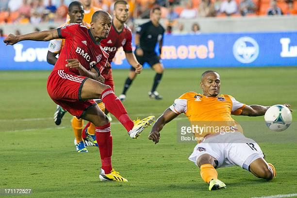 Robert Earnshaw of Toronto FC shoots past a diving Ricardo Clark of Houston Dynamo at BBVA Compass Stadium on June 22 2013 in Houston Texas