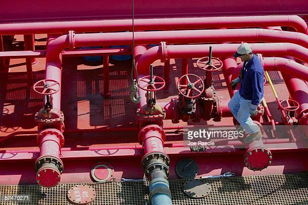 Robert Ezekiel checks on a hose being used to off-load fuel from a barge at the Global Petroleum facility April 27, 2006 in Boston, Massachusetts....