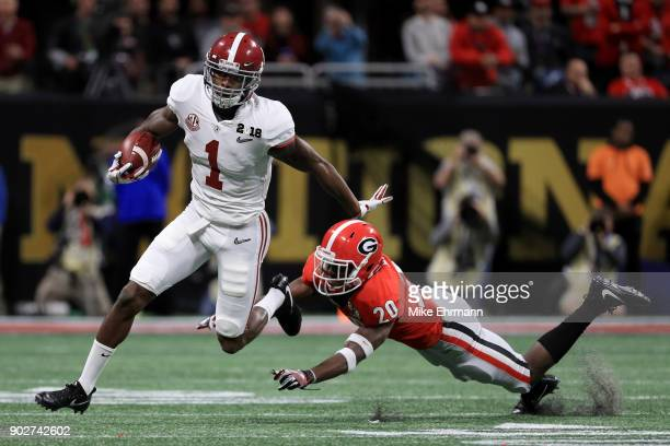 Robert Foster of the Alabama Crimson Tide stiff arms JR Reed of the Georgia Bulldogs on a run durign the first quarter in the CFP National...