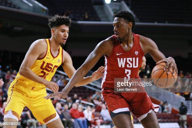 Robert Franks of the Washington State Cougars handles the ball against Bennie Boatwright of the USC Trojans during a PAC12 college basketball game at...