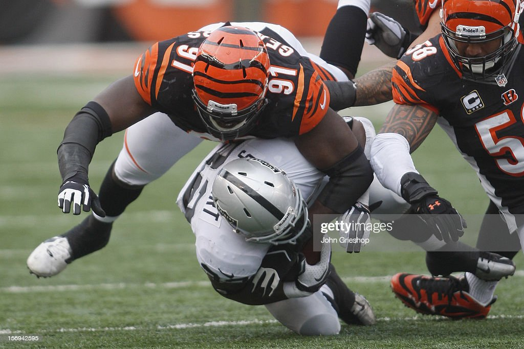 Robert Geathers #91 of the Cincinnati Bengals tackles Jeremy Stewart #32 of the Oakland Raiders during their game at Paul Brown Stadium on November 25, 2012 in Cincinnati, Ohio. The Bengals defeated the Raiders 34-10.