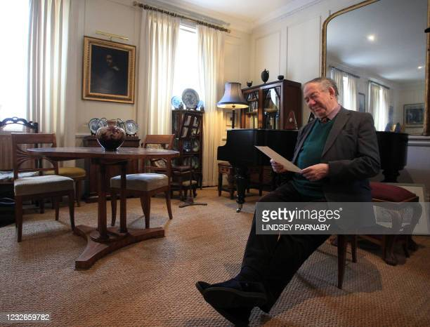 Robert Geoffrey William Anderson, retired British Museum curator and historian of chemistry, reacts as he holds a decree of Austrian citizenship...