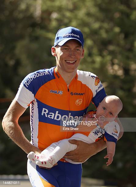 Robert Gesink of the Netherlands riding for Rabobank Cycling Team walks on to the podium with his daughter Anne to be awarded thhe yellow jersey...
