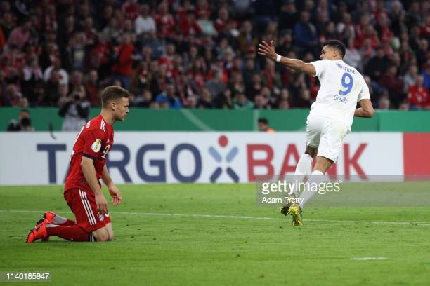 Robert Glatzel of Heidenheim celebrates his team's third goal next to Joshua Kimmich of Muenchen during the DFB Cup quarterfinal match between Bayern...
