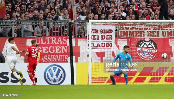 Robert Glatzel of Heidenheim scores his team's first goal past goalkeeper Sven Ulreich of Muenchen during the DFB Cup quarterfinal match between...