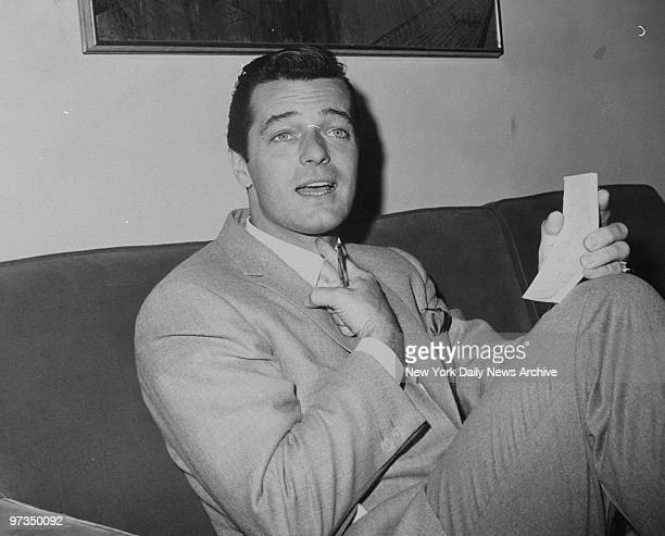 Robert Goulet sits on a couch at the Plaza Hotel as he indicates where the trouble is in his vocal cords after he was pulled out of a show in Ohio by...
