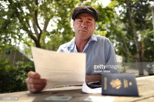 Robert Green holds his birth certificate and has his current passport and drivers license as he sits at his picnic table in his backyard in Wareham,...