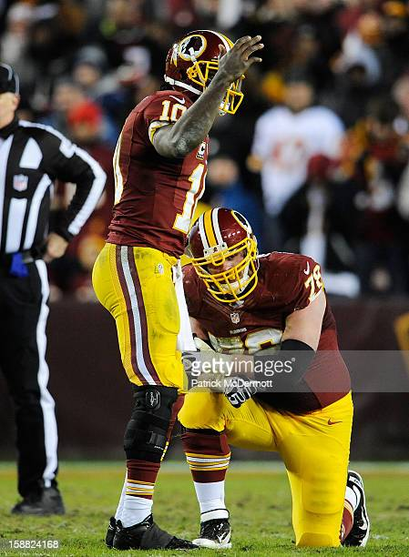 Robert Griffin III calls for trainers to come out for Kory Lichtensteiger of the Washington Redskins in the third quarter of their game against the...