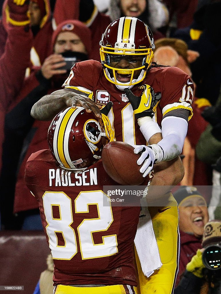 Robert Griffin III #10 celebrates his third quarter touchdown against the Dallas Cowboys with Logan Paulsen #82 of the Washington Redskins at FedExField on December 30, 2012 in Landover, Maryland.