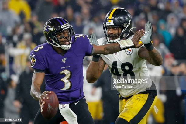Robert Griffin III of the Baltimore Ravens looks to pass as Bud Dupree of the Pittsburgh Steelers applies pressure during the first half at M&T Bank...