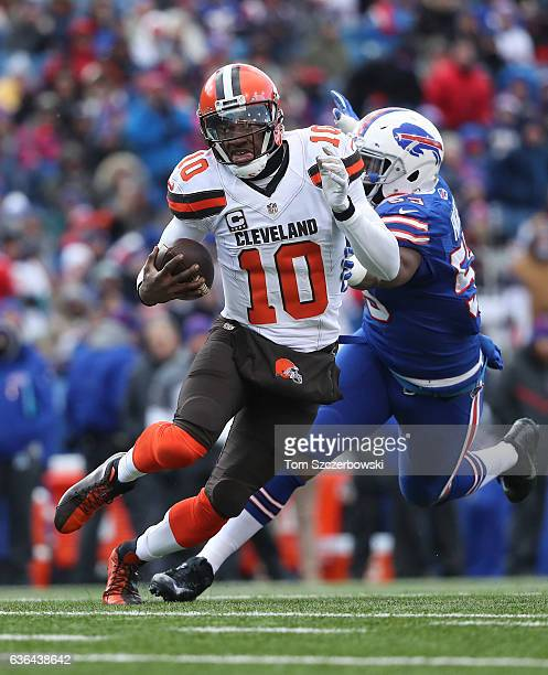 Robert Griffin III of the Cleveland Browns runs with the ball during NFL game action as he is chased by Jerry Hughes of the Buffalo Bills at New Era...