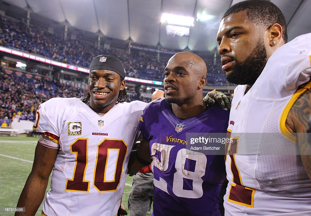 Robert Griffin III #10 of the Washington Redskins; Adrian Peterson #28 of the Minnesota Vikings and Trent Williams #71 of the Washington Redskins pose for a photo on November 7, 2013 at Mall of America Field at the Hubert Humphrey Metrodome in Minneapolis, Minnesota.
