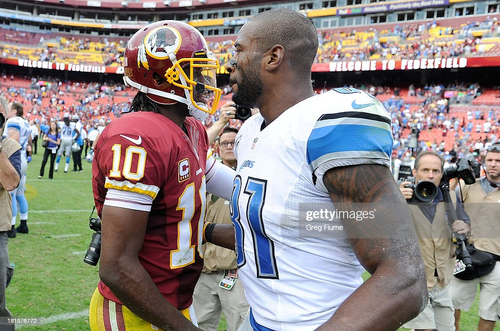 Robert Griffin III #10 of the Washington Redskins and Calvin Johnson #81 of the Detroit Lions talk after the game at FedExField on September 22, 2013 in Landover, Maryland. Detroit won the game 27-20.