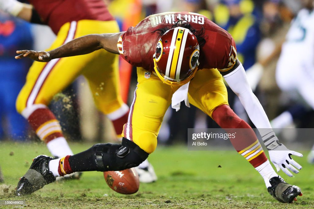 Robert Griffin III #10 of the Washington Redskins is injured as he fumbles a bad snap in the fourth quarter against the Seattle Seahawks during the NFC Wild Card Playoff Game at FedExField on January 6, 2013 in Landover, Maryland.