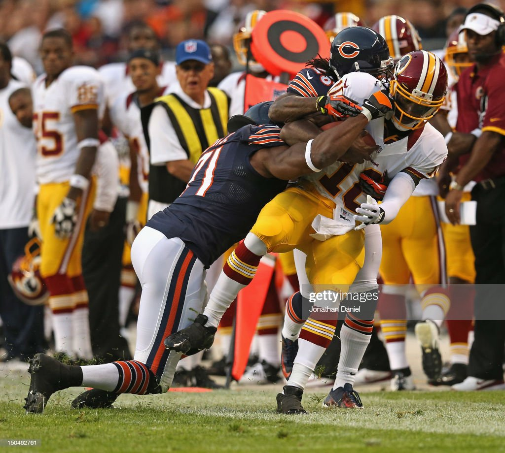 Robert Griffin III #10 of the Washington Redskins is knocked out of bounds by Israel Idonije #71 and Tim Jennings #26 of the Chicago Bears during a preseason game at Soldier Field on August 18, 2012 in Chicago, Illinois.