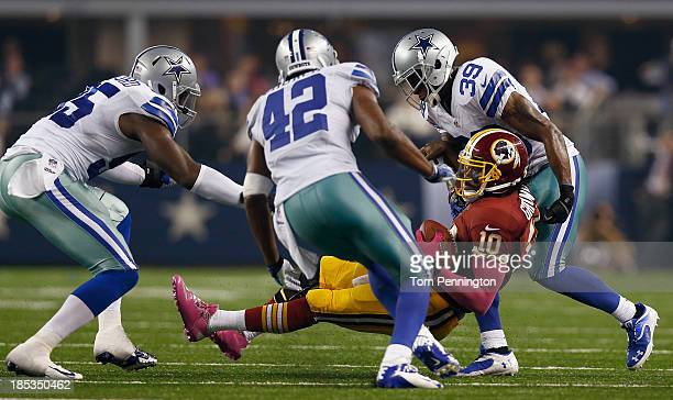 Robert Griffin III of the Washington Redskins is sacked by Caesar Rayford of the Dallas Cowboys Barry Church of the Dallas Cowboys and Brandon Carr...