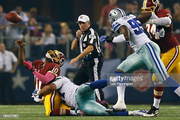 Robert Griffin III of the Washington Redskins is sacked by Jason Hatcher of the Dallas Cowboys for a loss in the second quarter on October 13 2013 in...