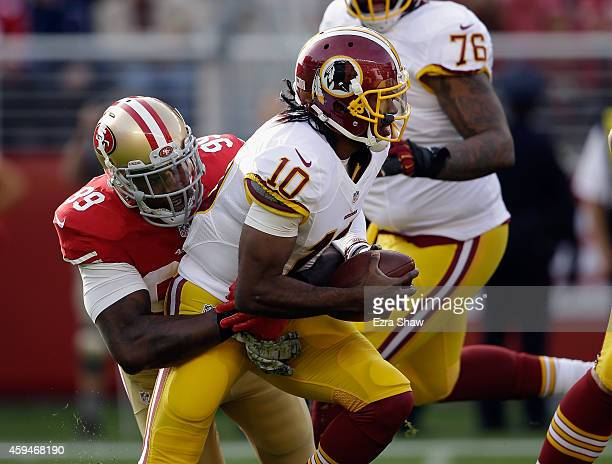 Robert Griffin III of the Washington Redskins is tackled by Aldon Smith of the San Francisco 49ers at Levi's Stadium on November 23 2014 in Santa...