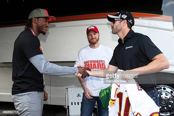 Robert Griffin III of the Washington Redskins presents Jimmie Johnson driver of the Kobalt Tools Chevrolet with a jersey as Dale Earnhardt Jr driver...