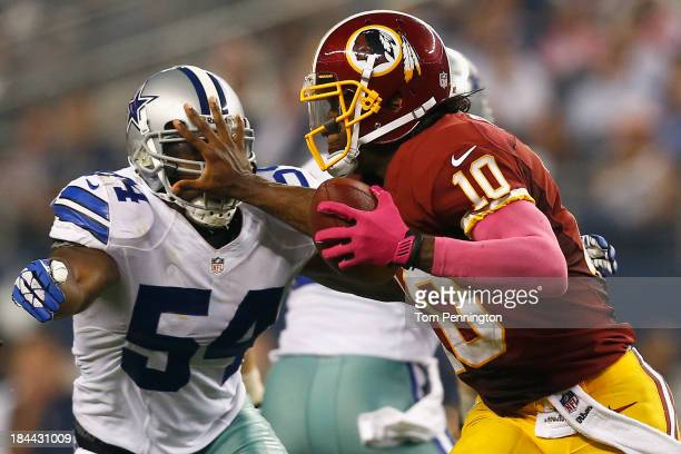 Robert Griffin III of the Washington Redskins scrambles with the ball against Bruce Carter of the Dallas Cowboys on October 13 2013 in Arlington...
