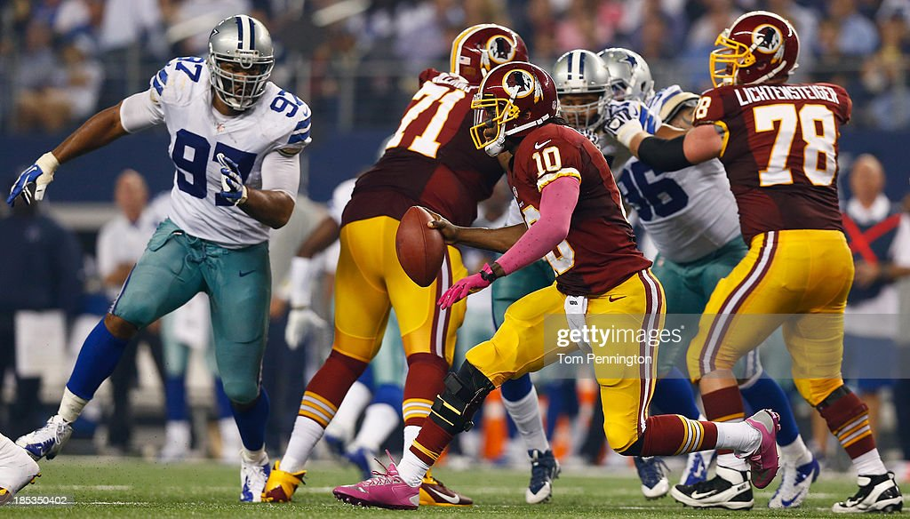 Robert Griffin III #10 of the Washington Redskins scrambles with the ball against Jason Hatcher #97 of the Dallas Cowboys in the fourth quarter on October 13, 2013 in Arlington, Texas. The Cowboys beat the Redskins 31-16.